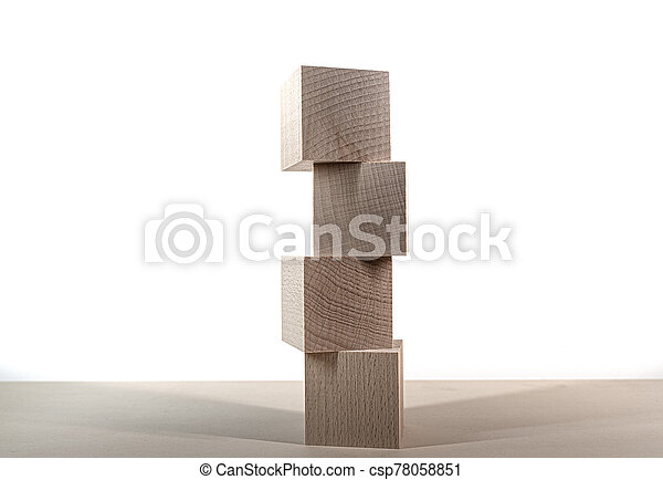 tower of four wooden blocks on table against white background - csp78058851