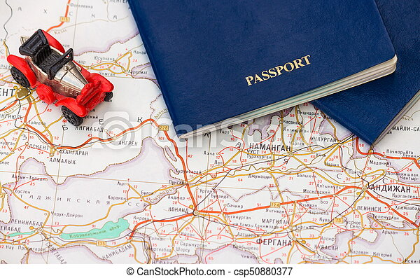 Toy car with two passports on the background of the map - csp50880377