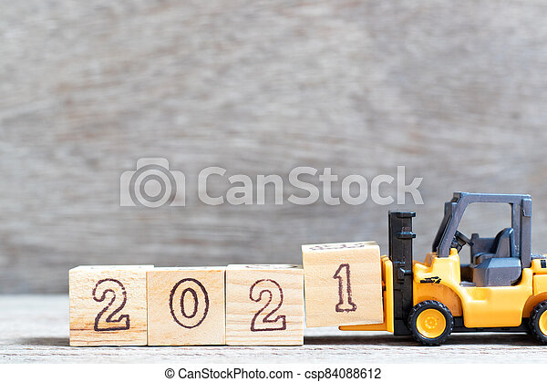 Toy forklift hold letter block 1 in word 2021 on wood background - csp84088612