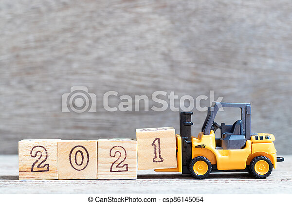 Toy forklift hold letter block 1 in word 2021 on wood background - csp86145054