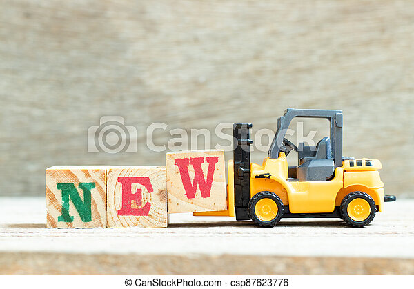Toy forklift hold letter block w to complete word new on wood background - csp87623776