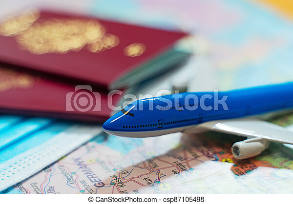 Toy of a plane, medical mask and passports on the Europe map. - csp87105498