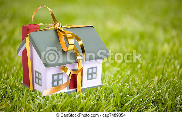 Toy small house with a gold bow. The concept of purchase and sale of habitation. - csp7489054