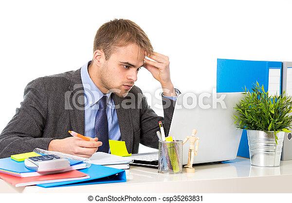 Un joven hombre de negocios con exceso de trabajo y preocupado sentado en el escritorio de la oficina con estrés - csp35263831