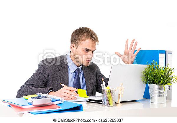 Un joven hombre de negocios con exceso de trabajo y preocupado sentado en el escritorio de la oficina con estrés - csp35263837