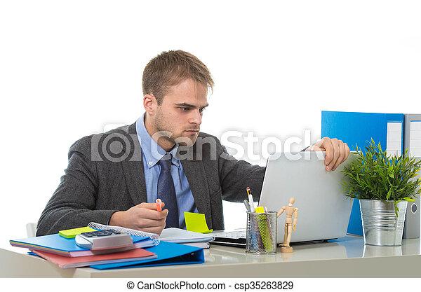 Un joven hombre de negocios con exceso de trabajo y preocupado sentado en el escritorio de la oficina con estrés - csp35263829