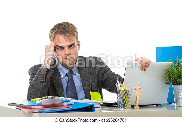 Un joven hombre de negocios con exceso de trabajo y preocupado sentado en el escritorio de la oficina con estrés - csp35264761