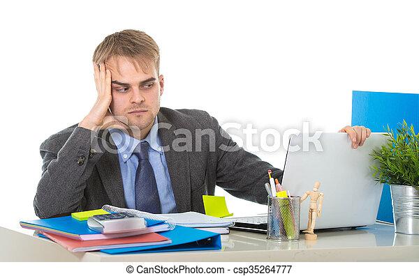 Un joven hombre de negocios con exceso de trabajo y preocupado sentado en el escritorio de la oficina con estrés - csp35264777