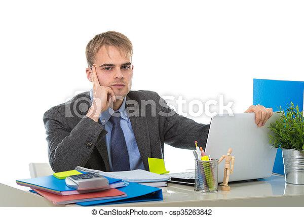 Un joven y cansado hombre de negocios sobrecargado de trabajo y molesto mirando preocupado sentado en el escritorio de la computadora - csp35263842