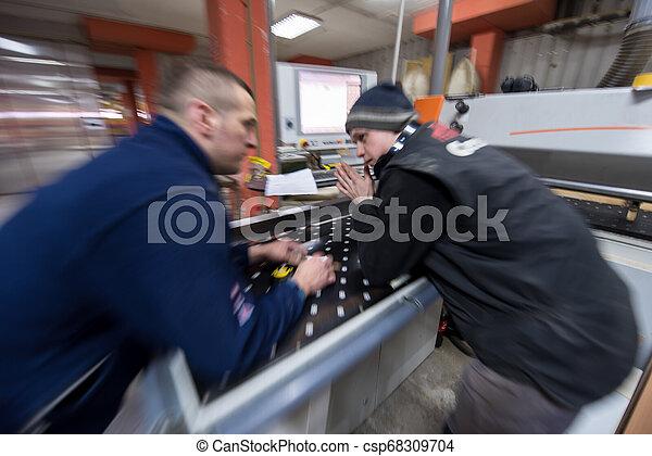 Carpinteros calculando y programando una máquina de madera CNC - csp68309704