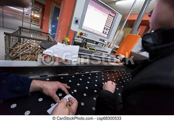 Carpinteros calculando y programando una máquina de madera CNC - csp68300533