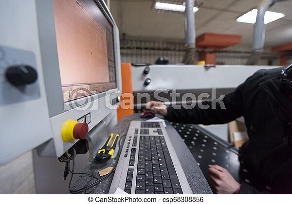 Carpinteros calculando y programando una máquina de madera CNC - csp68308856