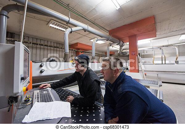 Carpinteros calculando y programando una máquina de madera CNC - csp68301473