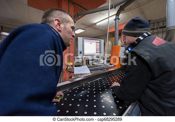 Carpinteros calculando y programando una máquina de madera CNC - csp68295289