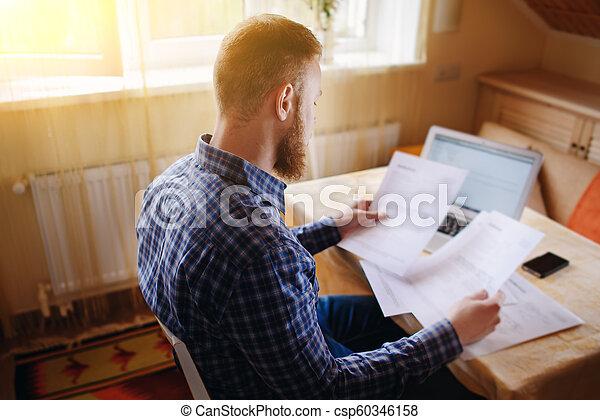 Hombre de negocios en casa, está trabajando con un portátil, revisando papel - csp60346158