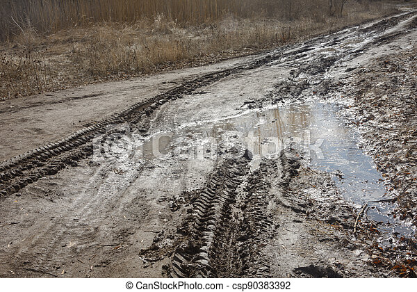Track from car tire in dirt road in spring. Traces of stuck vehicles in liquid mud. Danger to driving - csp90383392