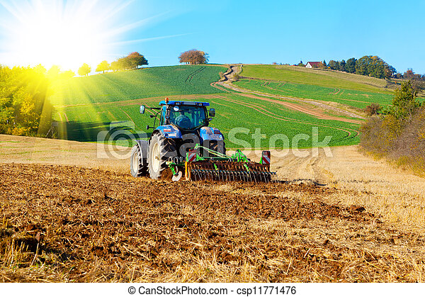 Tractor plows a field in the spring, with sunlight - csp11771476