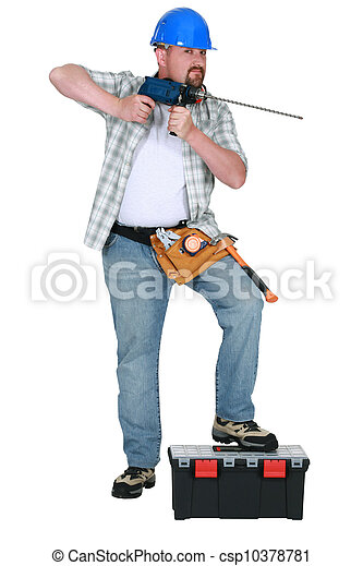 Tradesman holding a drill with a long bit - csp10378781