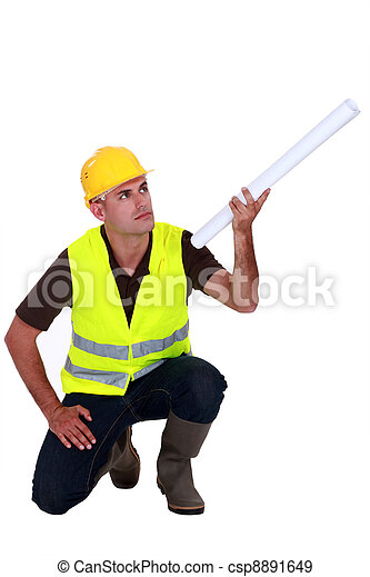 Tradesman holding up a rolled-up blueprint - csp8891649