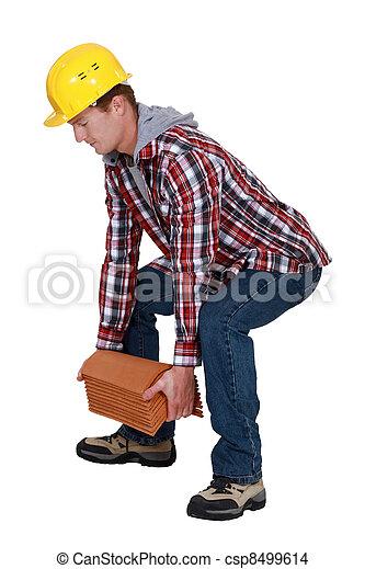 Tradesman lifting shingles - csp8499614