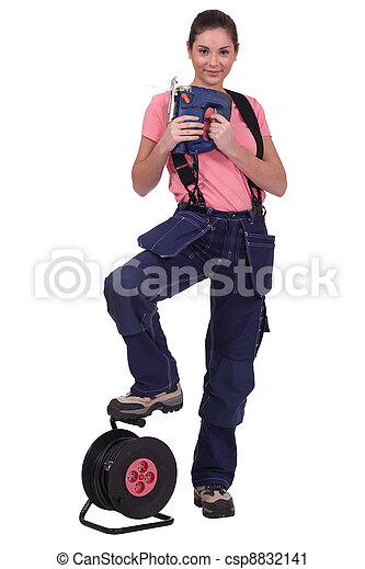 Tradeswoman holding a jigsaw with her foot propped on an extension reel - csp8832141