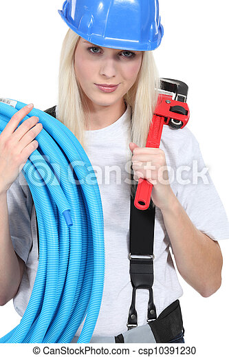 Tradeswoman holding corrugated tubing and a pipe wrench - csp10391230