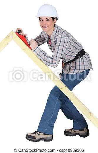 Tradeswoman using a plane to smooth a wooden frame - csp10389306