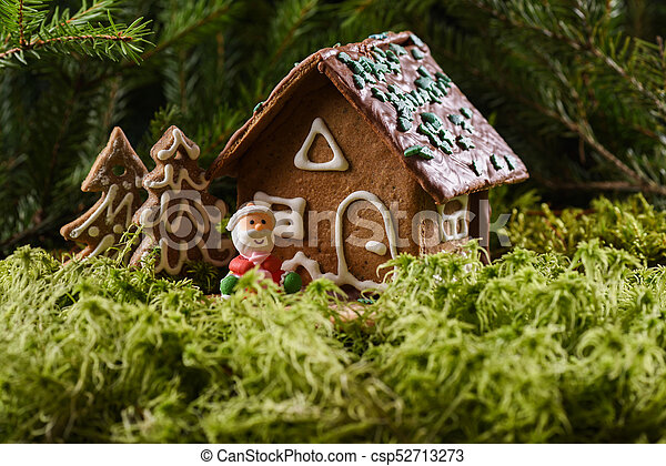Traditional Christmas Gingerbread House Cookies And Happy Smiling Marzipan Santa Claus In Green Forest Moss