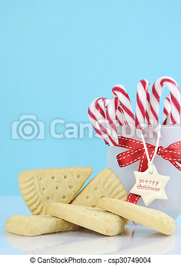 Traditional Christmas shortbread triangle shape cookies with jar of candy canes against a pale blue and white background. Vertical with copy space. - csp30749004