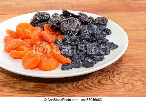 Traditional dried fruits on dish closeup at selective focus - csp58046063