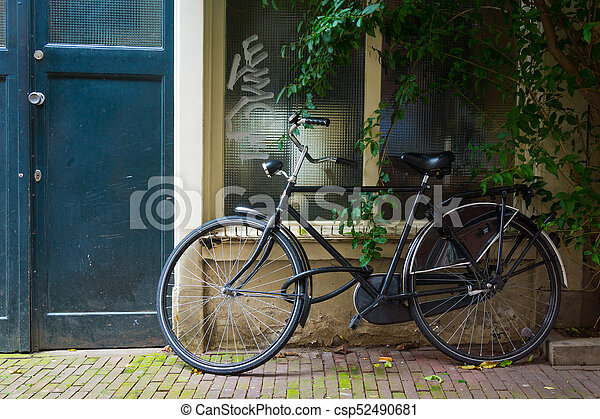 Traditional dutch bicycle parked at the front door in Amsterdam - csp52490681
