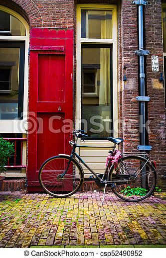 Traditional dutch bicycle parked at the front door in Amsterdam - csp52490952