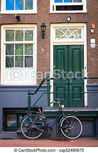 Traditional dutch bicycle parked on near brick wall in Amsterdam - csp52490670