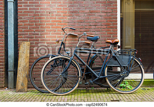 Traditional dutch bicycle parked on near brick wall in Amsterdam - csp52490674