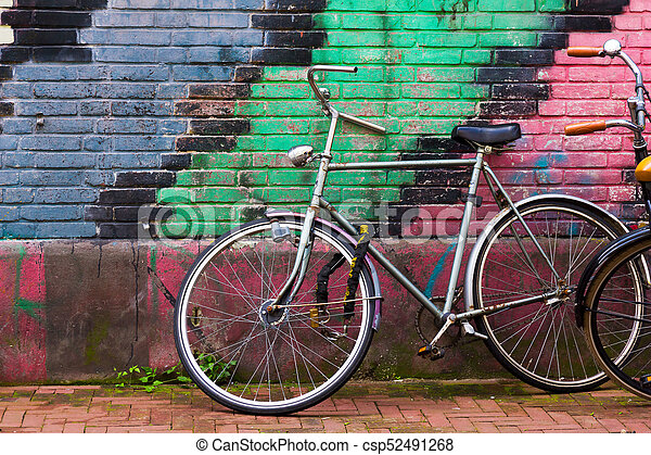 Traditional dutch bicycle parked on near brick wall in Amsterdam - csp52491268