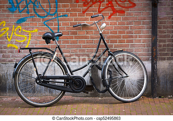 Traditional dutch bicycle parked on near brick wall in Amsterdam - csp52495863
