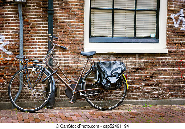 Traditional dutch bicycle parked on near brick wall in Amsterdam - csp52491194