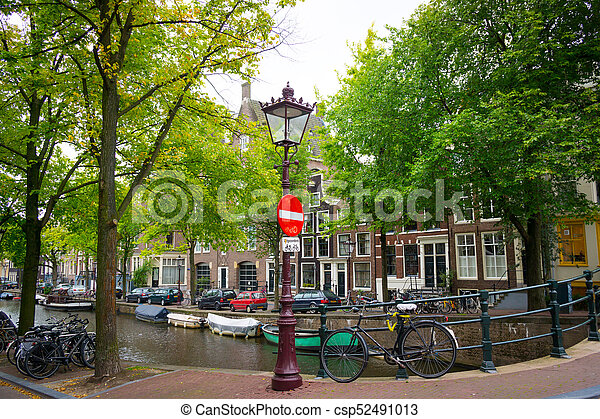 Traditional dutch bicycle parked on canal in Amsterdam - csp52491013