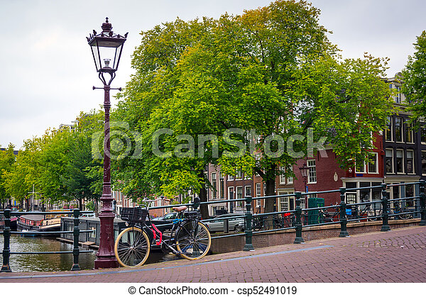 Traditional dutch bicycle parked on canal in Amsterdam - csp52491019