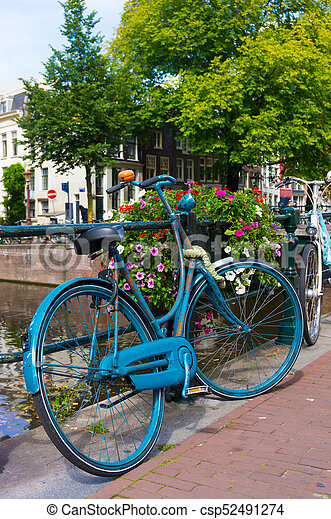 Traditional dutch bicycle parked on canal in Amsterdam - csp52491274