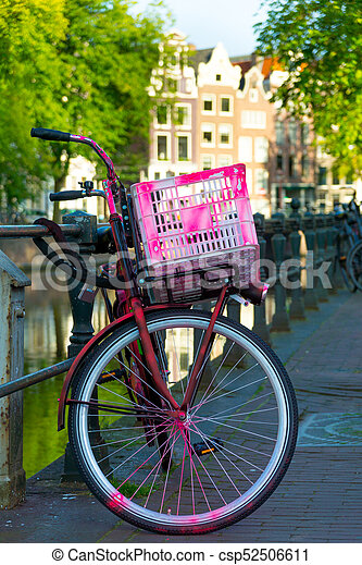 Traditional dutch bicycle parked on canal in Amsterdam - csp52506611