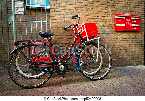 Traditional dutch bicycles parked on near brick wall in Amsterdam - csp52490908