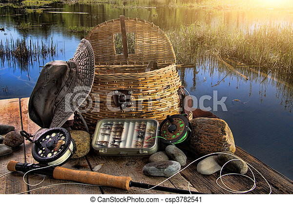 Traditional fly-fishing rod with equipment in late afternoon - csp3782541