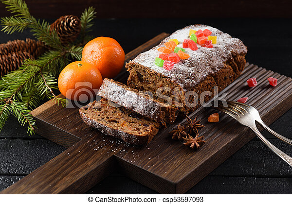 Traditional fruit cake for Christmas served on wooden board with clementines on black background - csp53597093