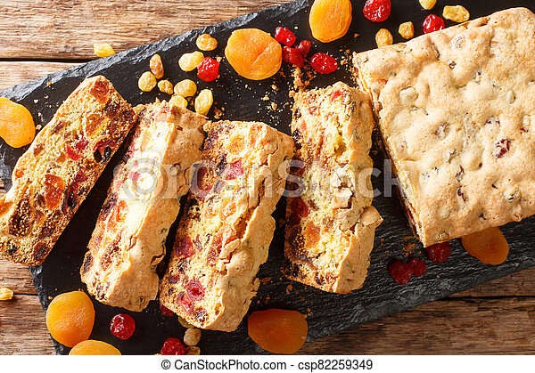 Traditional fruit cake with dried apricots berries raisins figs cherries closeup on a slate board. horizontal top view - csp82259349