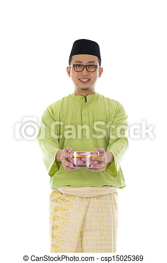 Traditional Malay male with biscuit during hari raya - csp15025369