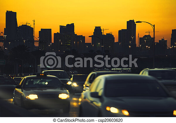 Traffic at nightfall in city with Miami Skyline on background. - csp20603620