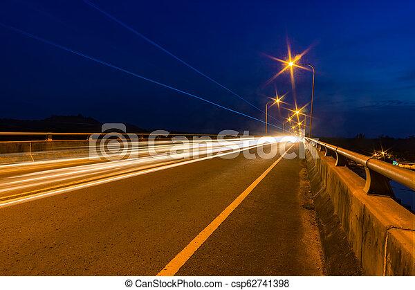Traffic light trails at night on a bridge. - csp62741398