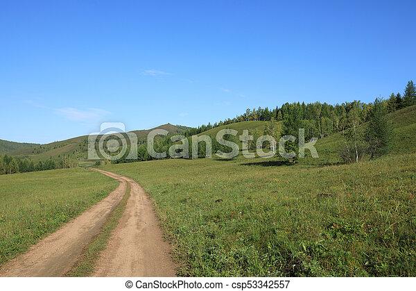 trail on green grassland under blue sky - csp53342557