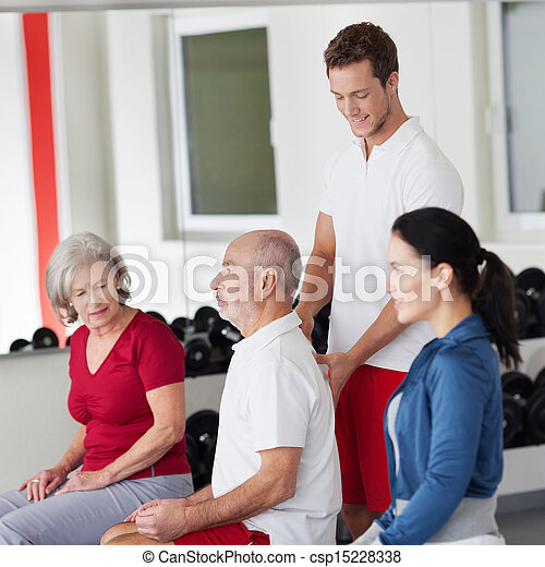 Trainer correcting the posture of an elderly man - csp15228338